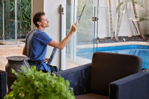 Technicien en nettoyage de vitres qui nettoie une vitre